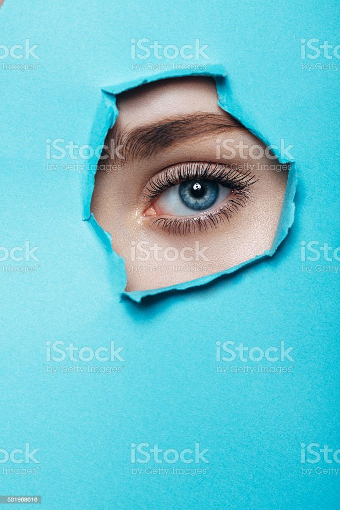 Girl watches through a hole in cardboard stock photo