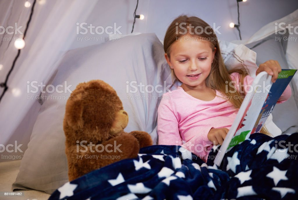 Girl watching a picture book with a teddy bear stock photo