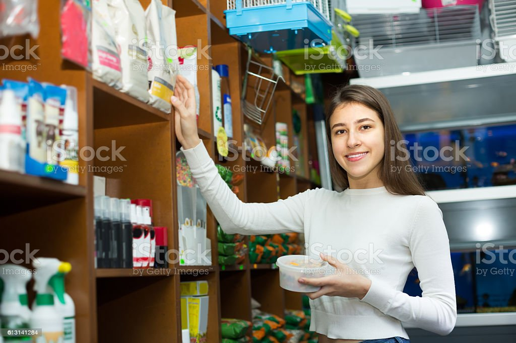Girl watching dry food in pet store stock photo