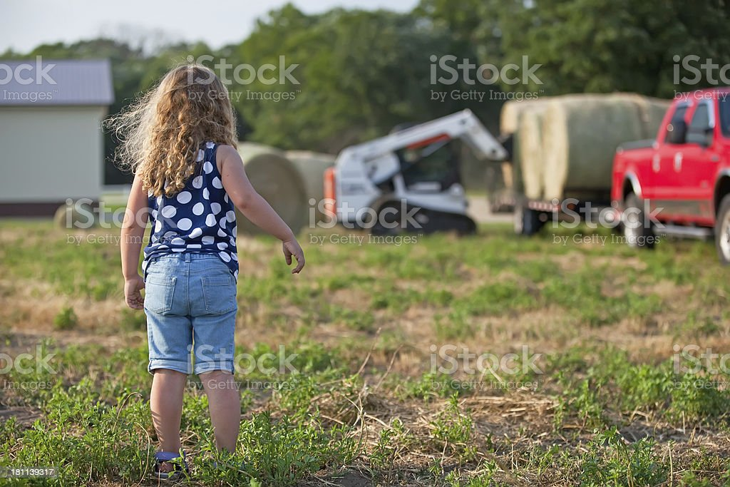 Girl Watching Hay Bales Being Loaded on Trailer stock photo