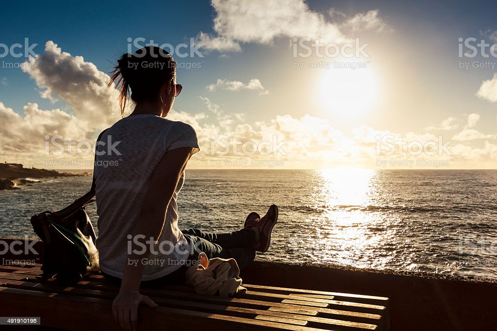 Girl Watching Sunset at Sea in Easter Island, Chile stock photo