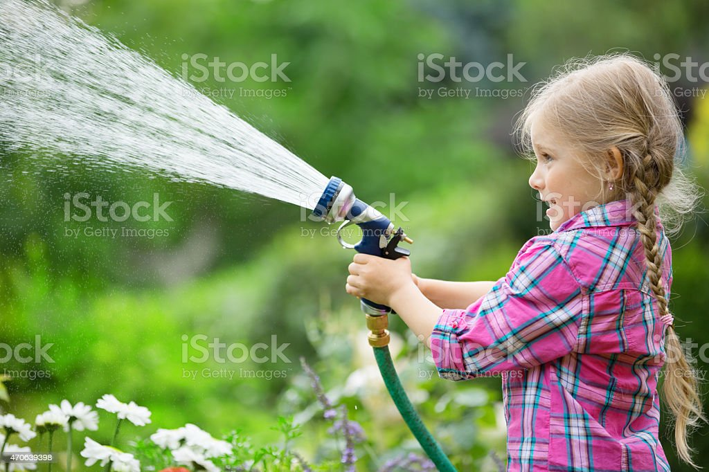 Girl watering flowers in garden with hose stock photo