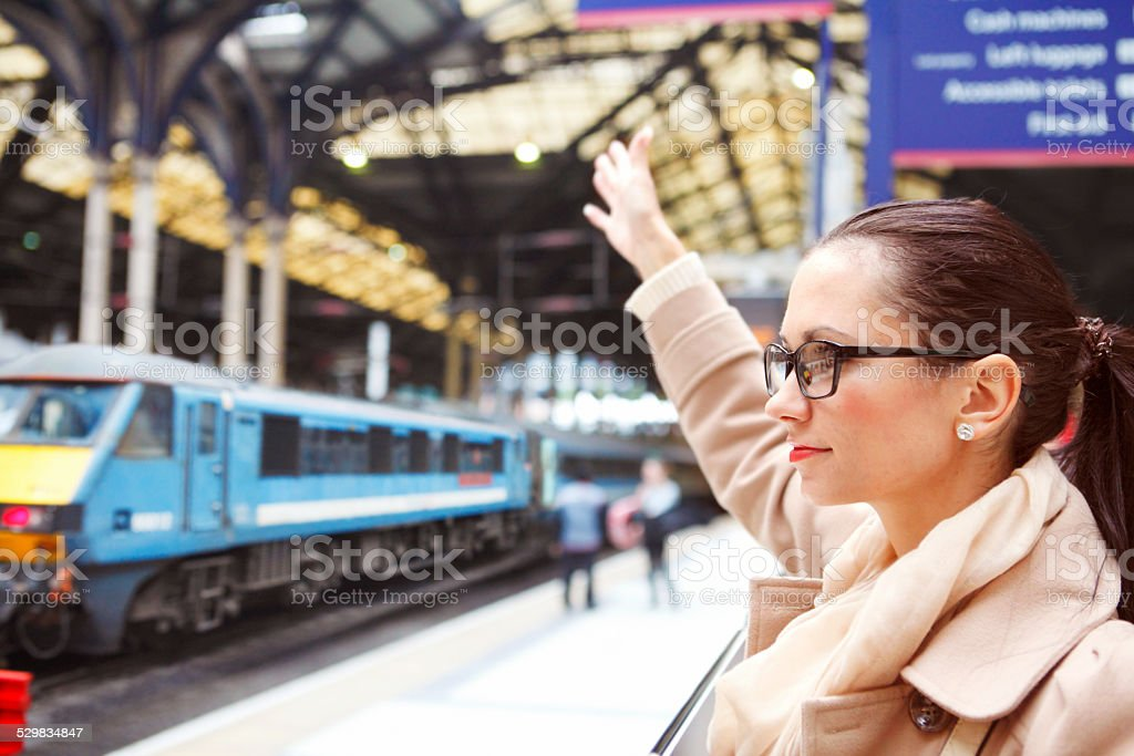 Girl waving at somebody in railway station stock photo
