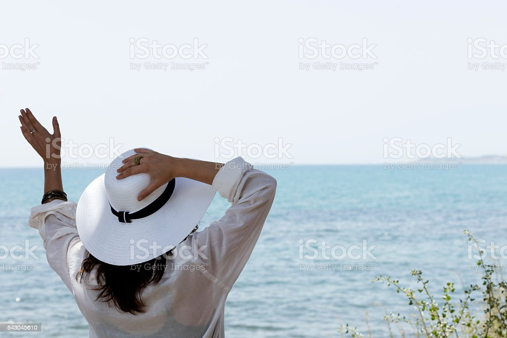 girl waving in front of the sea stock photo