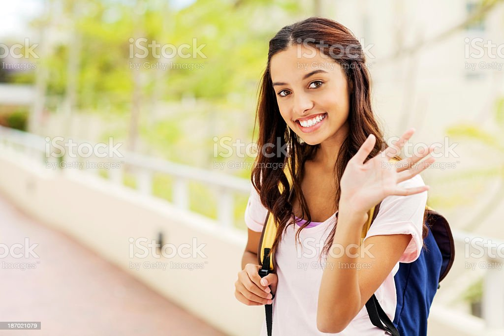 Girl Waving While Carrying Backpack On College Sidewalk royalty-free stock photo