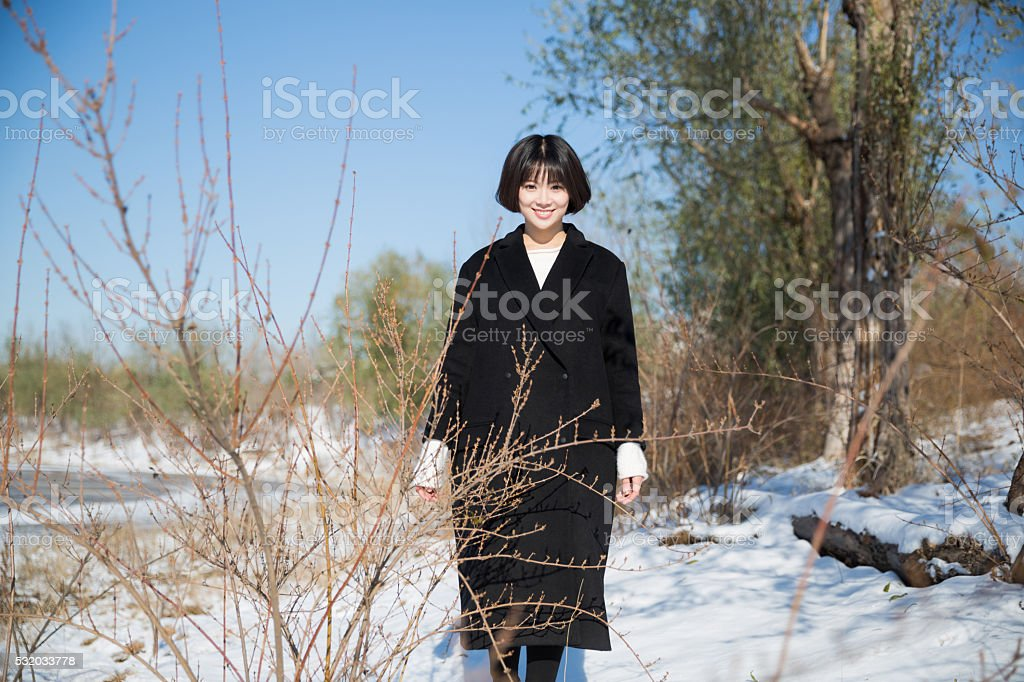 girl wearing a black winter coat stock photo