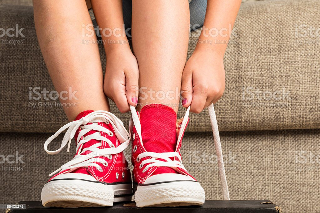 Girl wearing a pair of red sneakers stock photo
