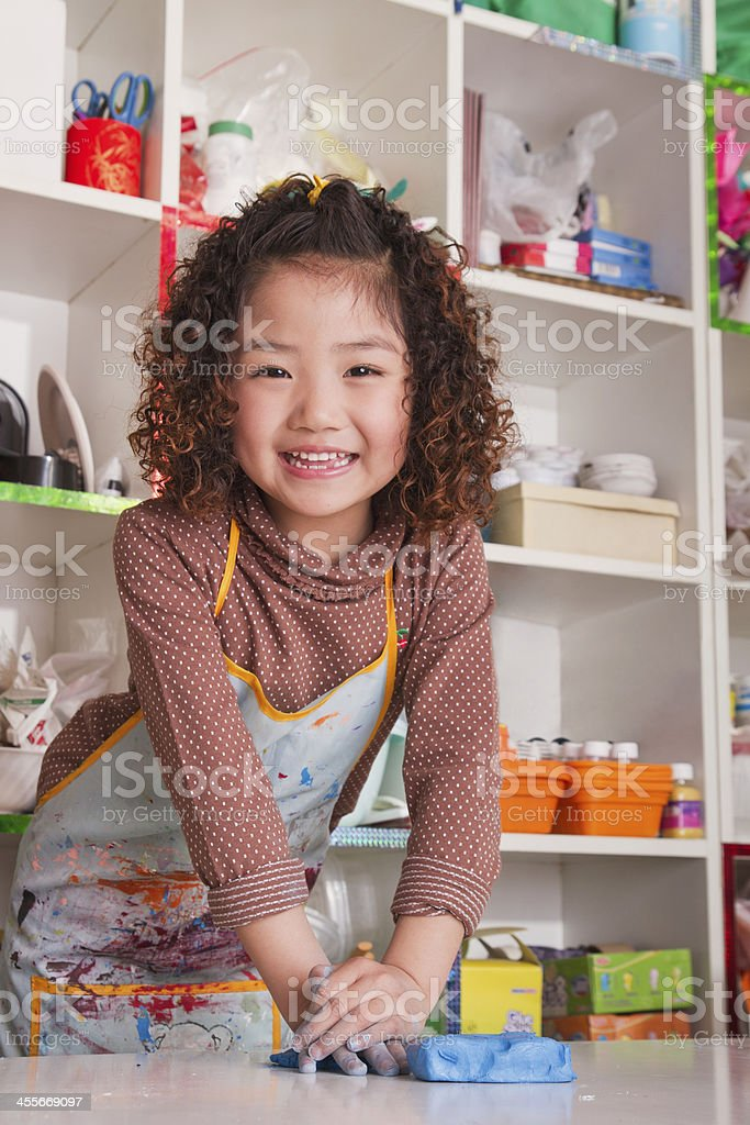 Girl Wearing Apron and Playing with Clay stock photo