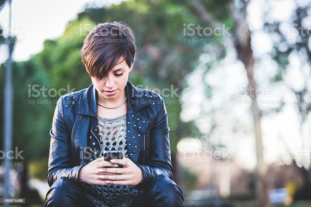 Girl wearing black leather jacket typing on smartphone royalty-free stock photo