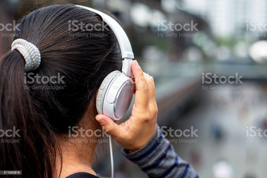 girl wearing earphone,listening music in downtown stock photo