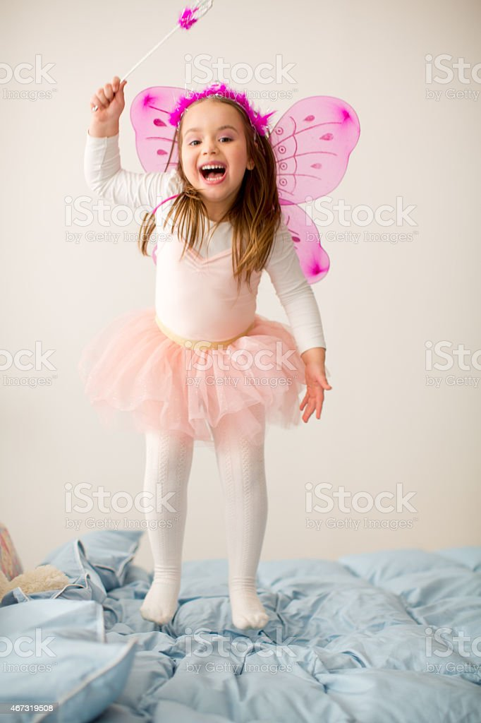 Girl wearing fairy costume jumping on bed. stock photo
