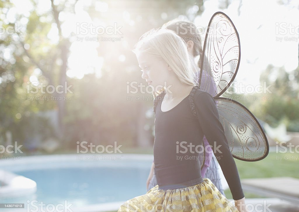 Girl wearing fairy wings in backyard royalty-free stock photo