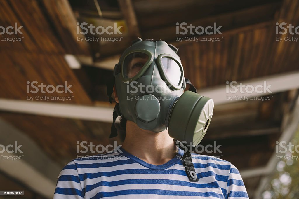 Girl wearing gas mask in front of ruined building portrait stock photo