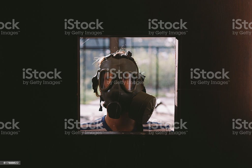Girl wearing gas mask looking through abandoned buildings door opening stock photo