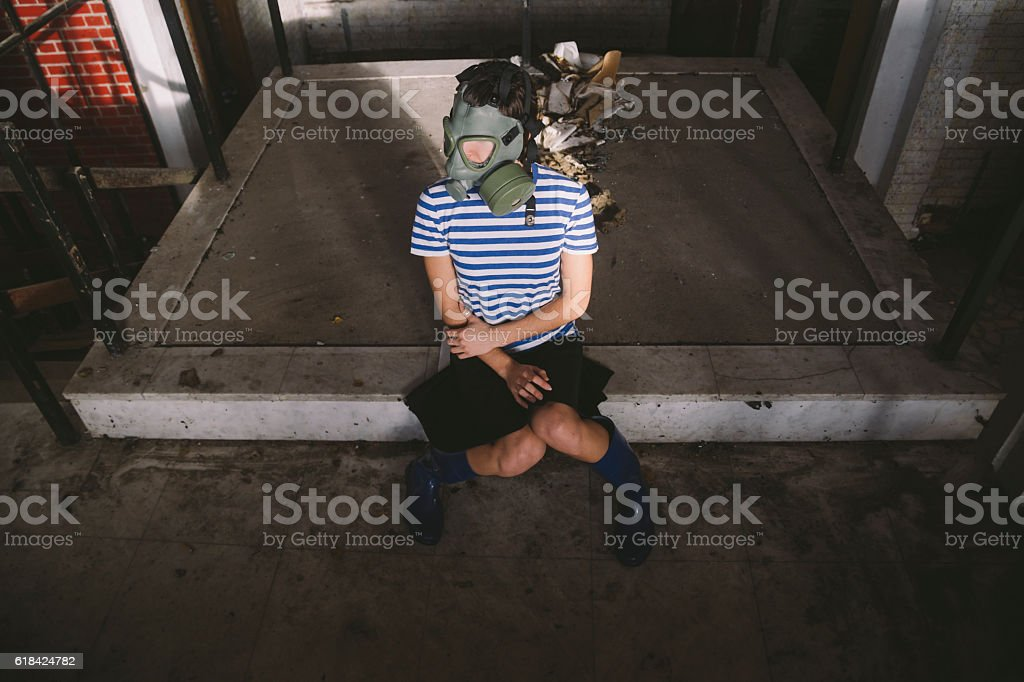 Girl wearing gas mask sitting at ruined building hall stock photo