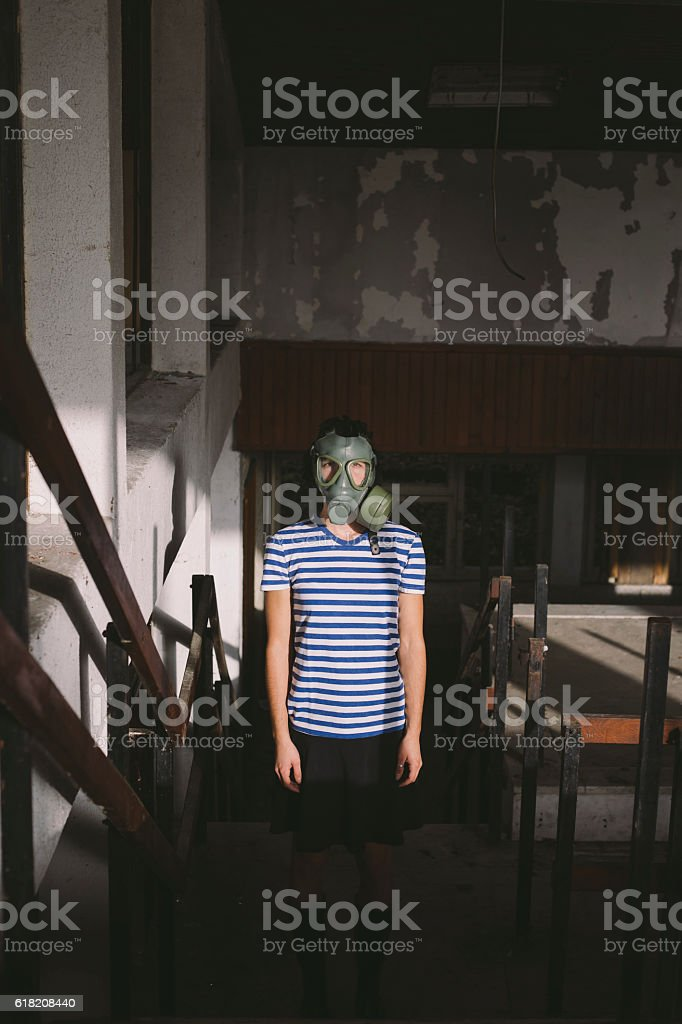 Girl wearing gas mask standing in dark, ruined hall stock photo
