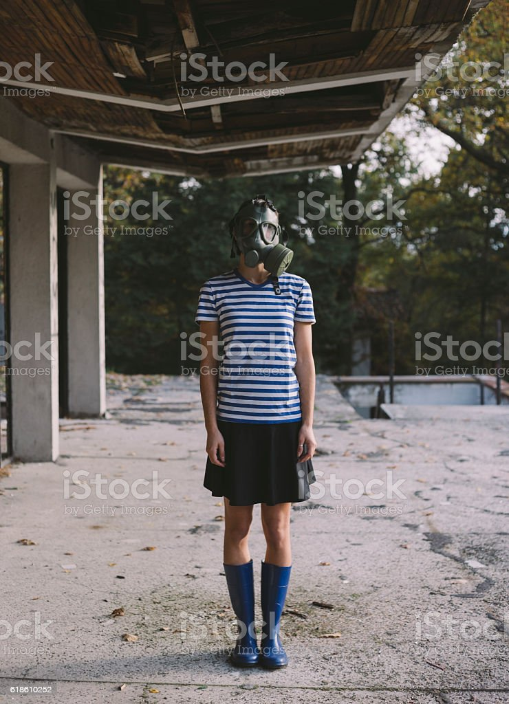 Girl wearing gas mask standing on balcony of ruined building stock photo