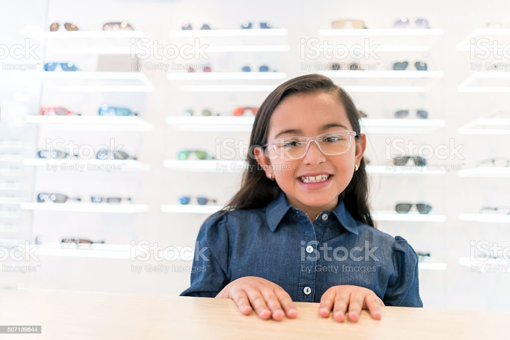 Girl wearing glasses at the optician's shop stock photo
