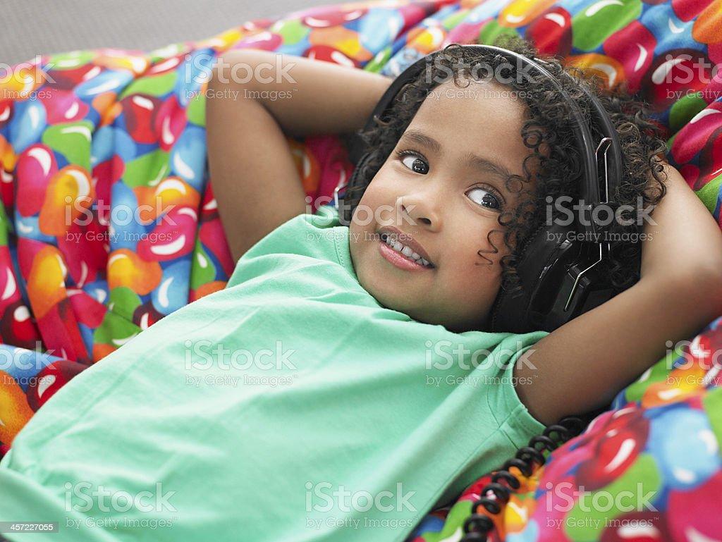 Girl Wearing Headphones Reclining On Beanbag stock photo