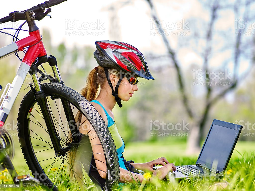 Girl wearing helmet in cycling near bicycle with pc tablet. stock photo