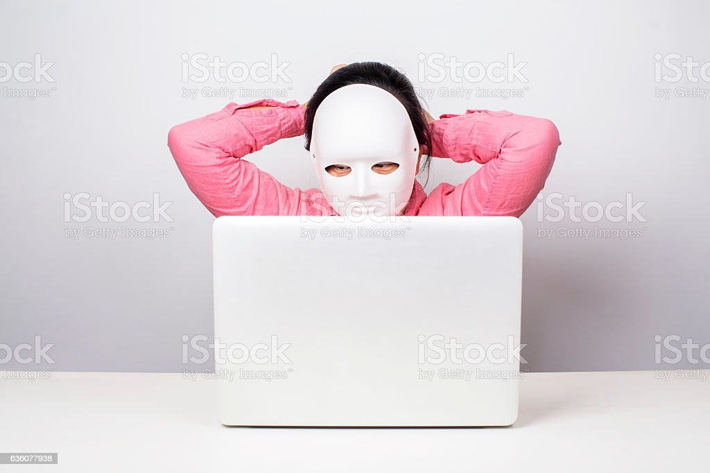girl wearing mask in front of laptop stock photo