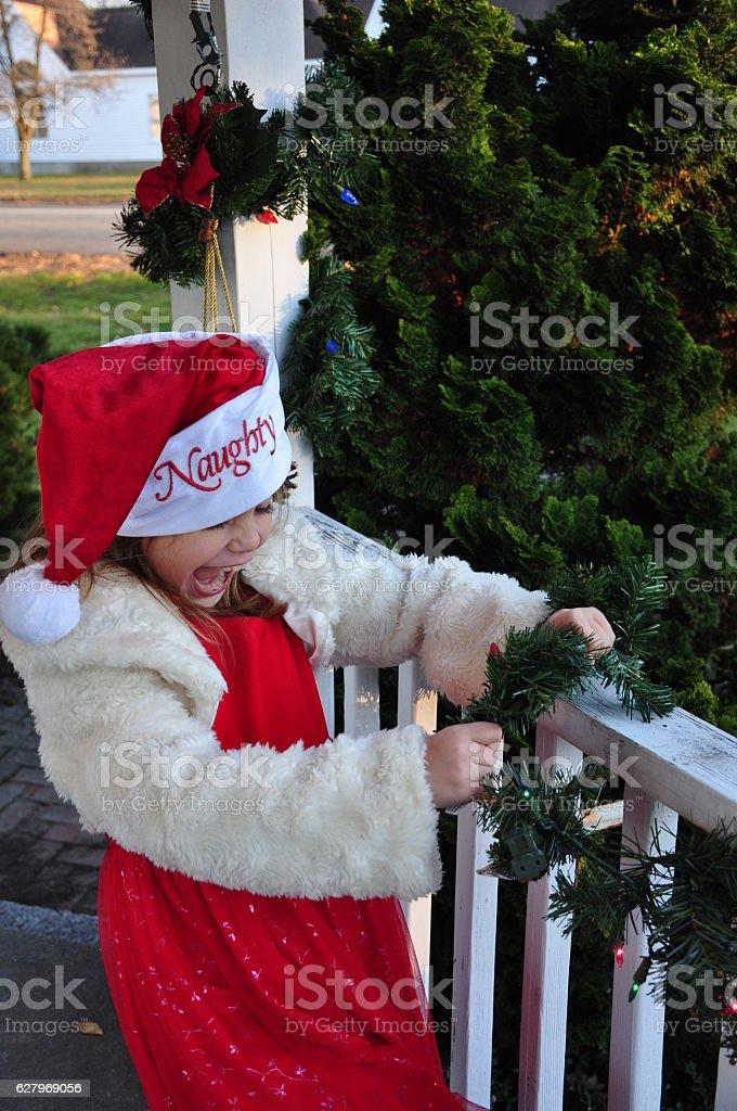 Girl Wearing Naughty Santa Hat Screaming and Wrecking Christmas Decorations stock photo