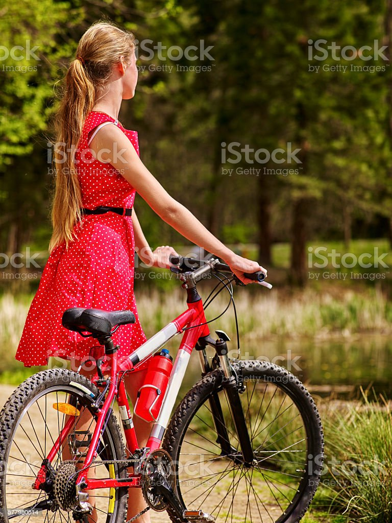 Girl wearing red dress rides bicycle in park. stock photo