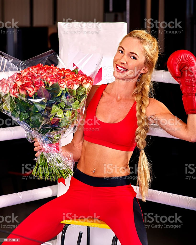 Girl wearing red gloves sitting in corner of boxing ring stock photo