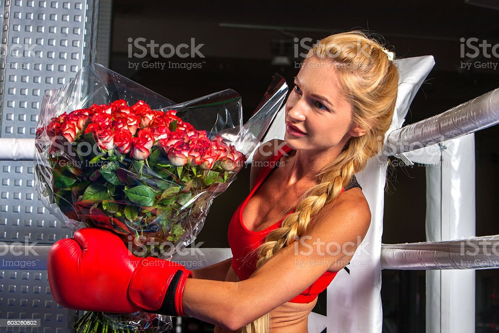 Girl wearing red gloves sitting in corner of boxing ring. stock photo