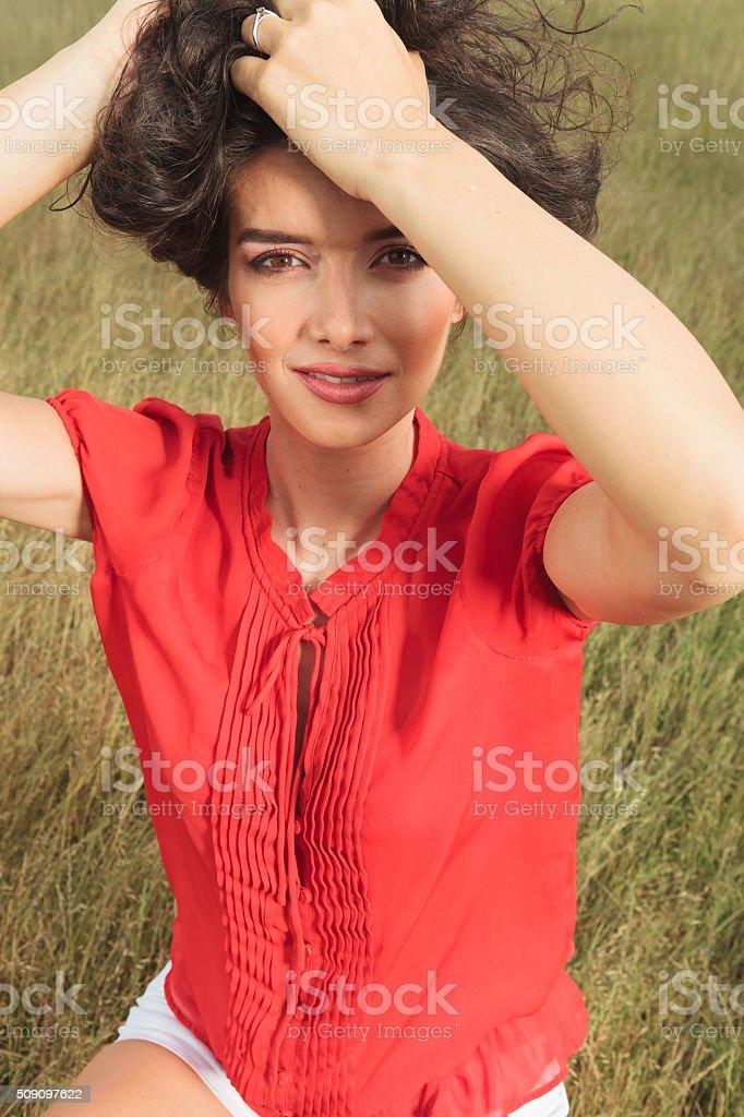 girl wearing short pants, fixing her hair while sitting stock photo