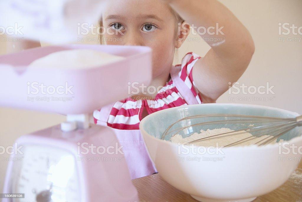 Girl weighing ingredients in kitchen stock photo
