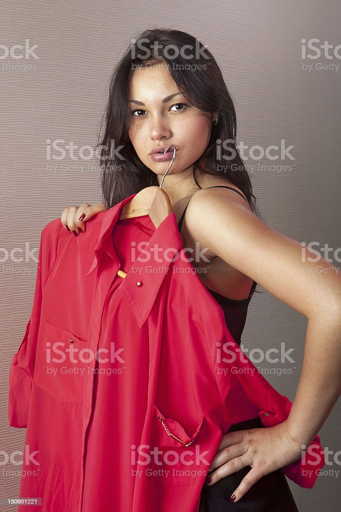girl which tries on red shirt in shop stock photo