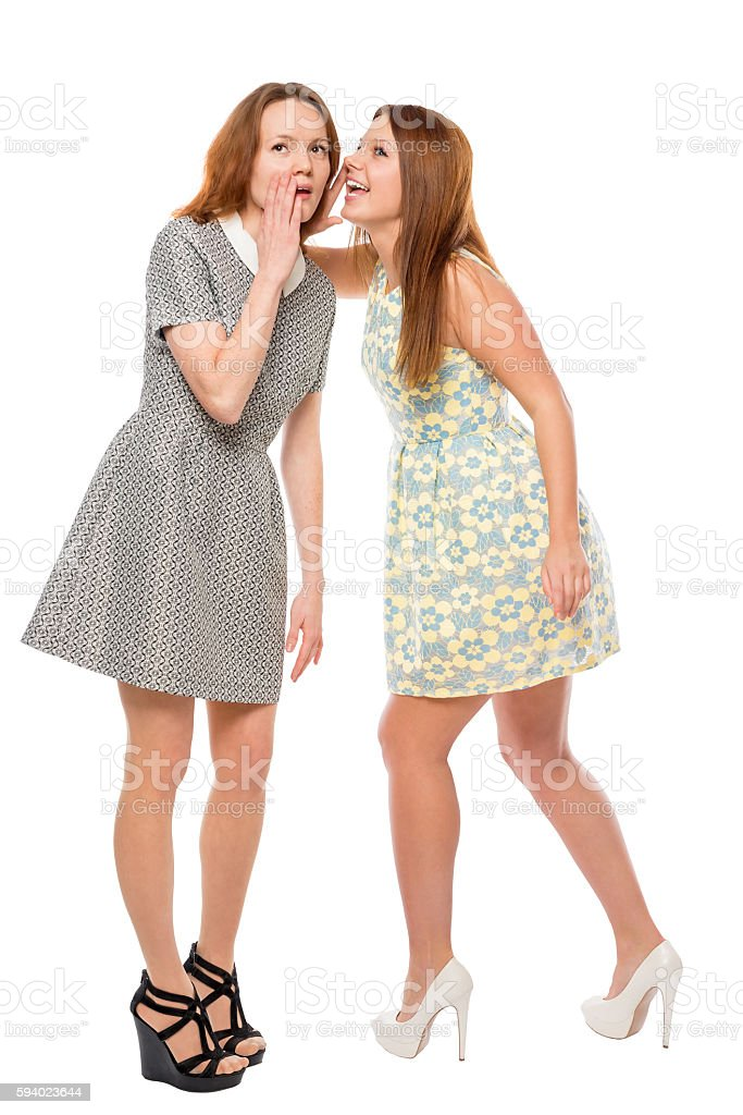 Girl whispering a secret to her friend stock photo