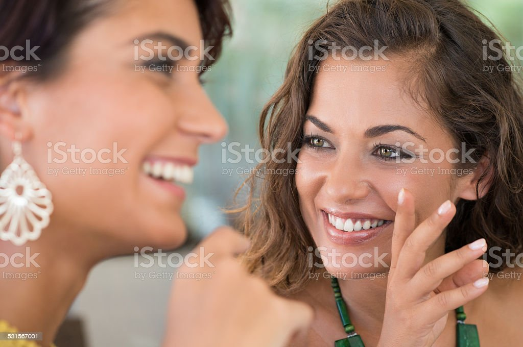 Girl Whispering Secret To A Friend stock photo