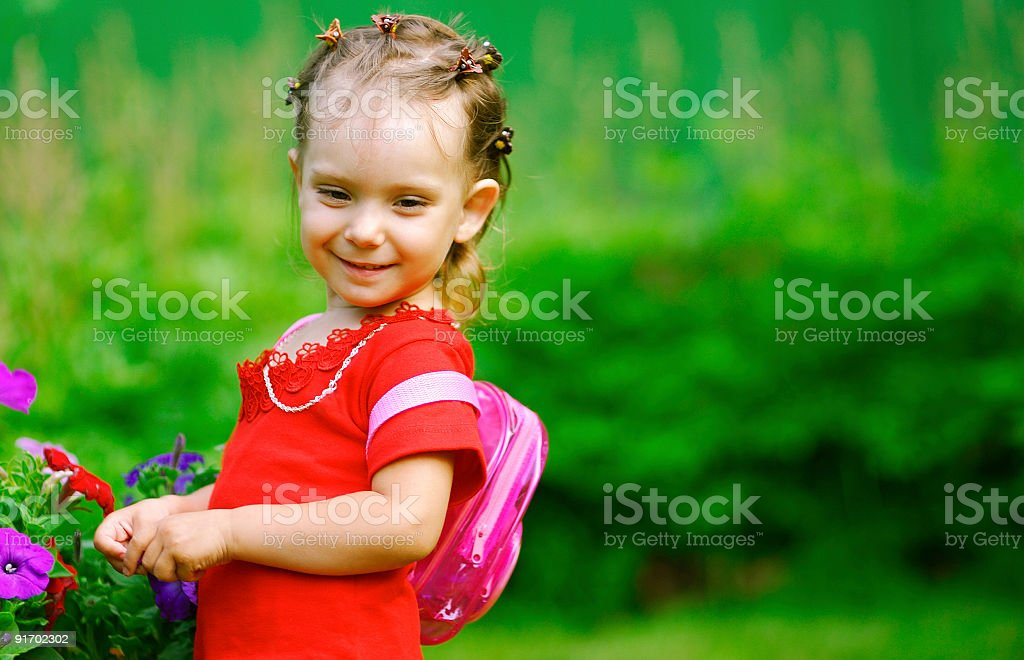 Girl with a backpack about florets royalty-free stock photo