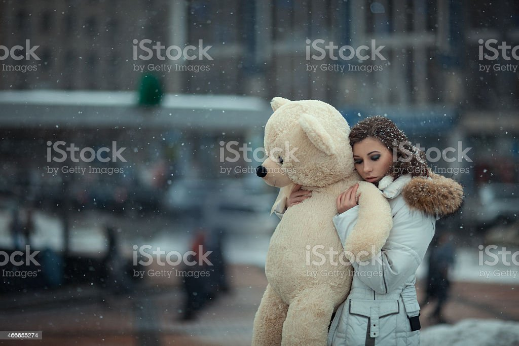 Girl with a bear during snow. stock photo