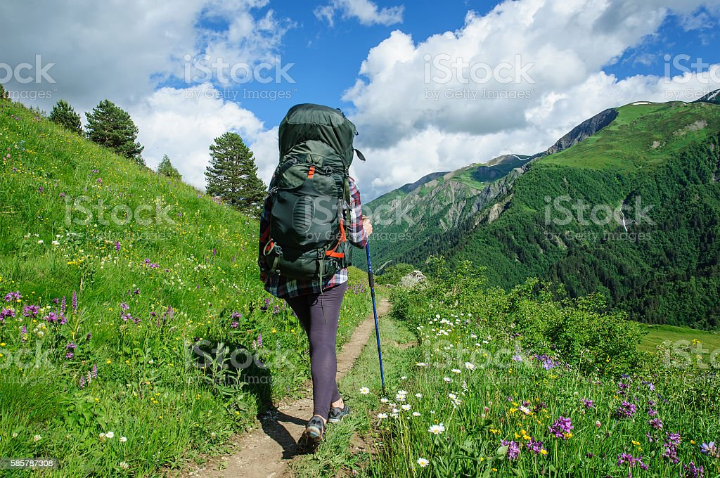 Girl with a big backpack is traveling in the Caucasus stock photo