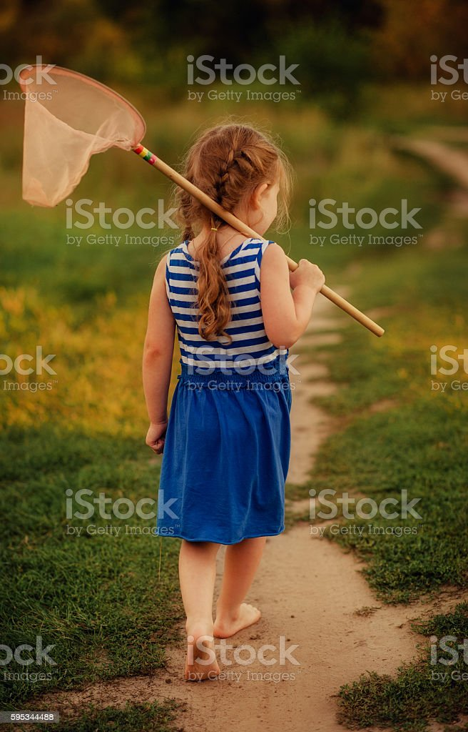 girl with a butterfly net goes barefoot about the grass stock photo