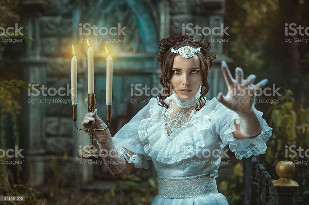 Girl with a candelabra in hand terrifies. stock photo