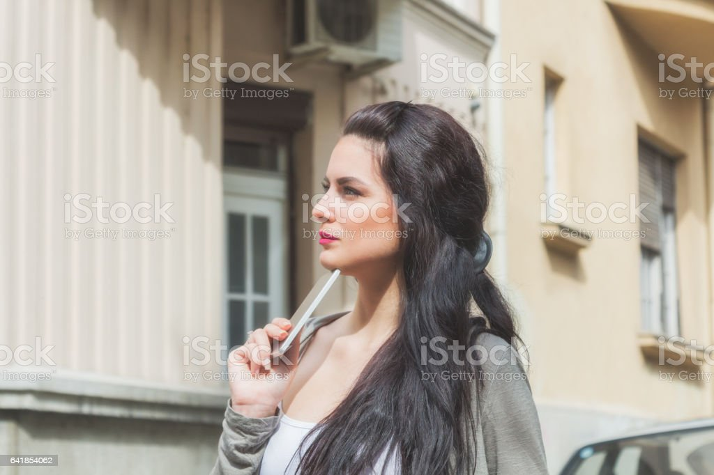 Girl with a cellphone outdoors. stock photo