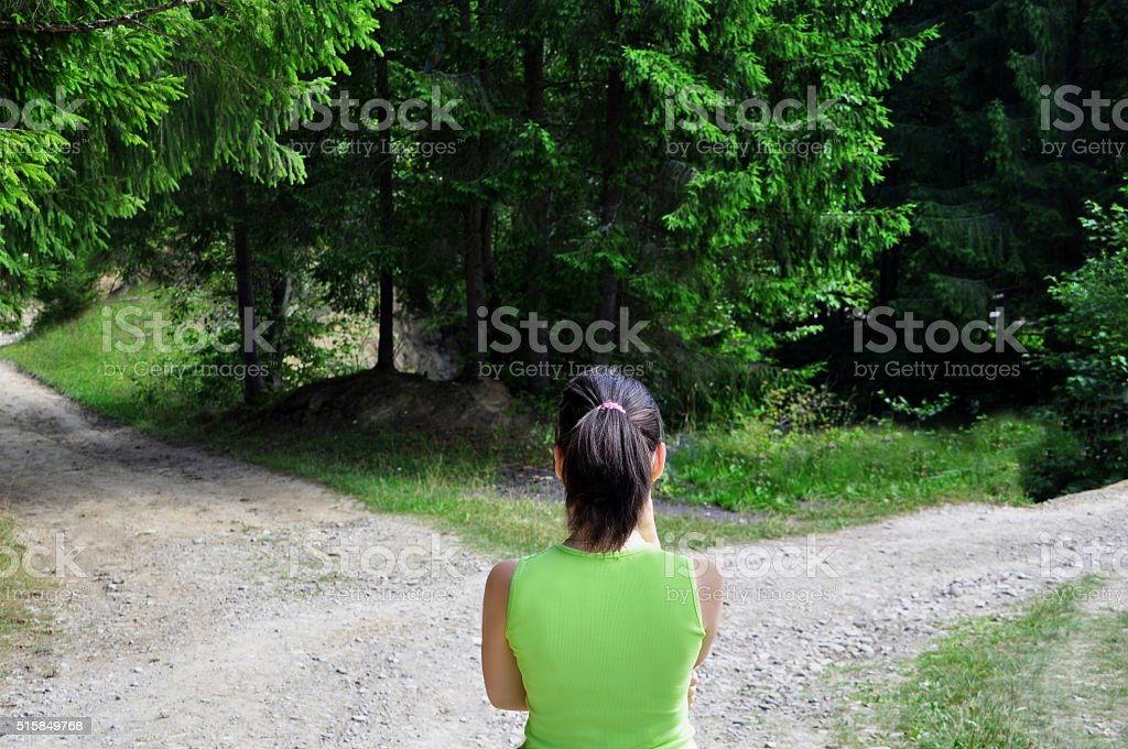 Girl with a choice near the forked road stock photo