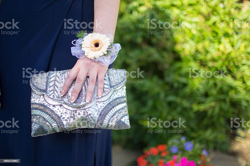Girl with a corsage holding a clutch bag stock photo