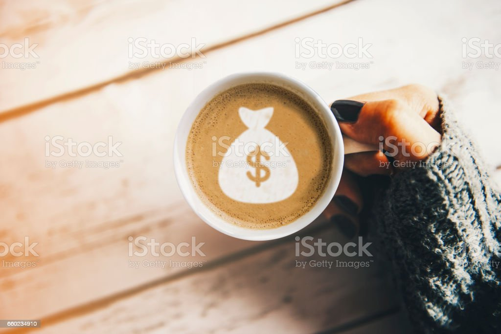 Girl with a cup of coffee with a money bag symbol stock photo