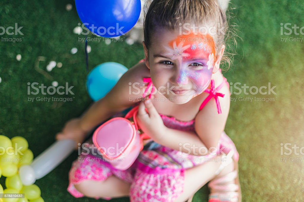 girl with a face paint on a kids party celebration stock photo