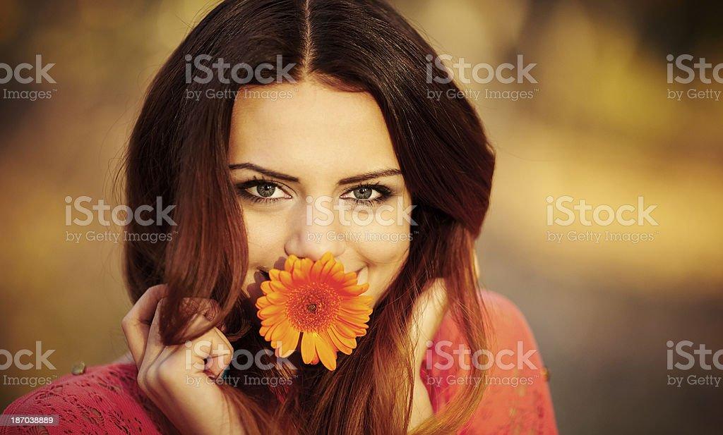 Ragazza con un fiore in bocca foto stock royalty-free