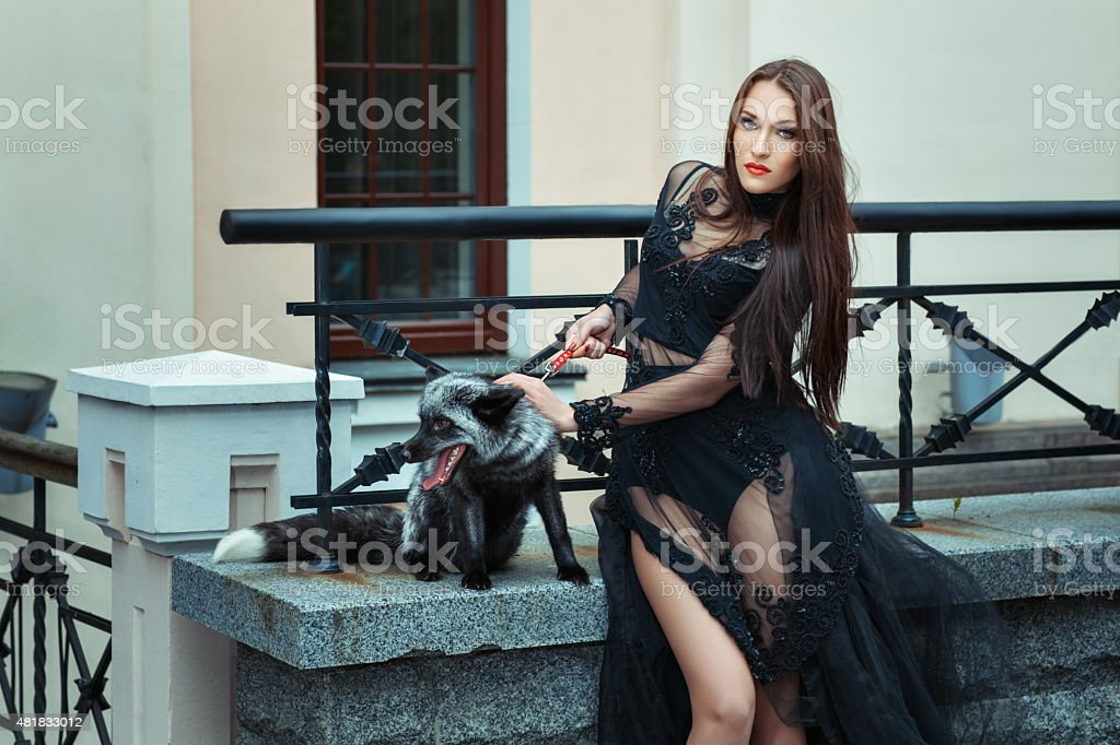 Girl with a fox on the balcony. stock photo