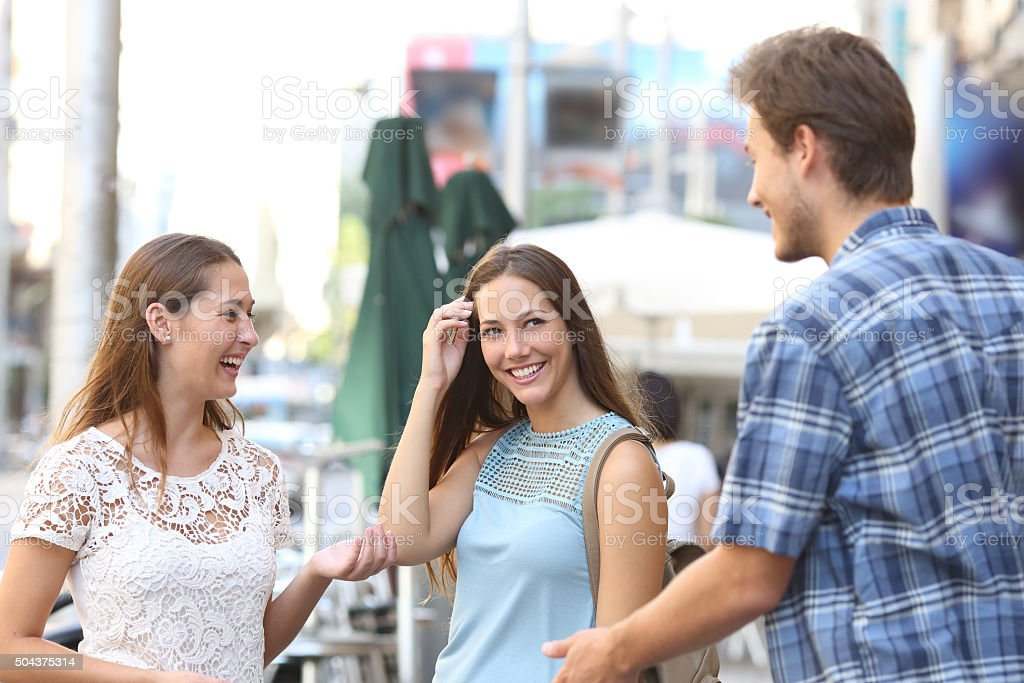 Girl with a friend flirting with a boy stock photo