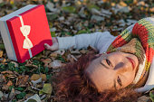 Girl with a gift in hand lying on the leaves