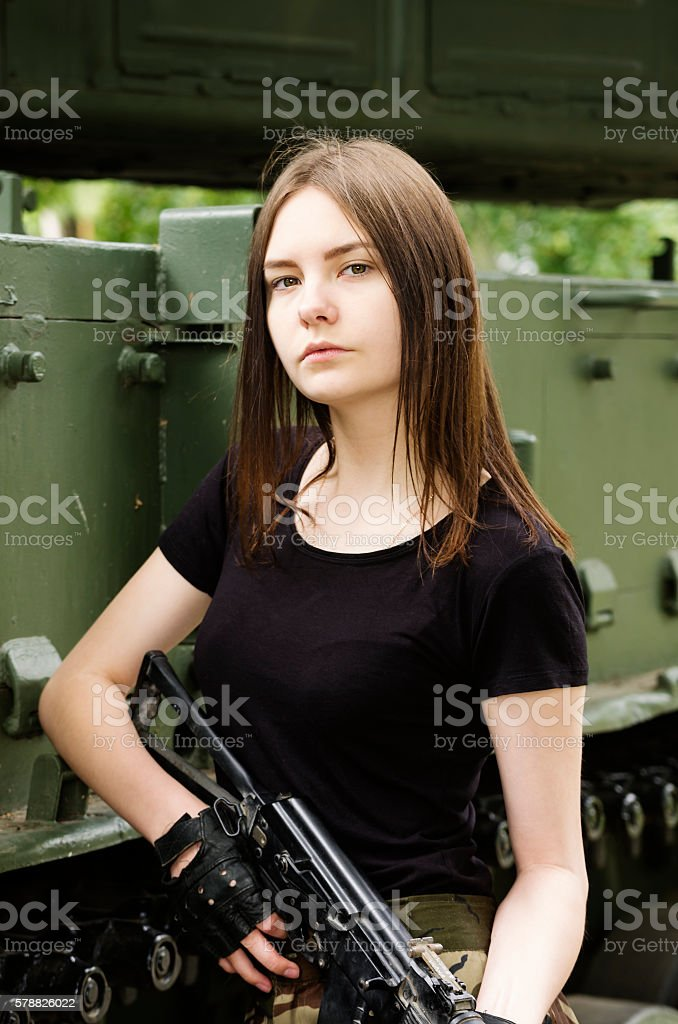Girl with a gun, posing near the armored vehicle stock photo