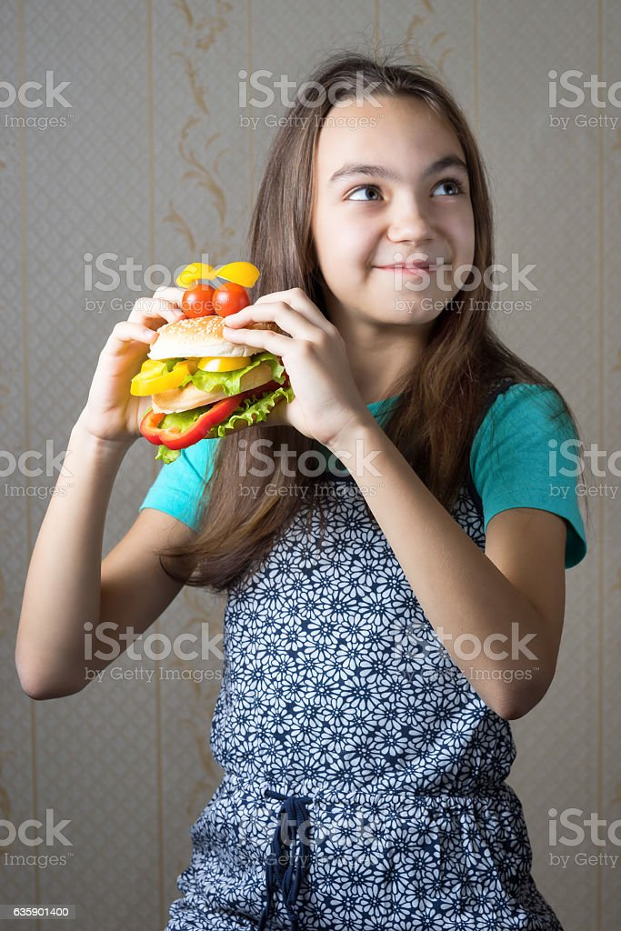 girl with a hamburger in hand looking up stock photo